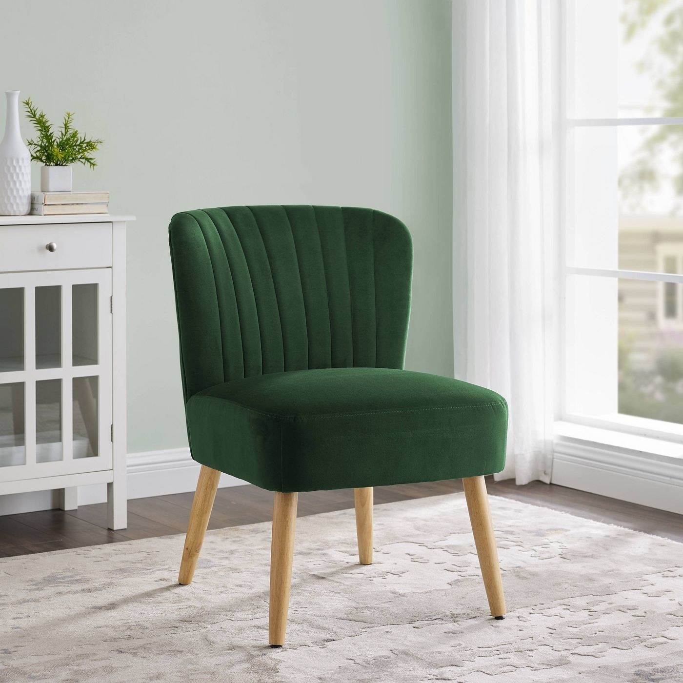 A green velvet chair with wood legs