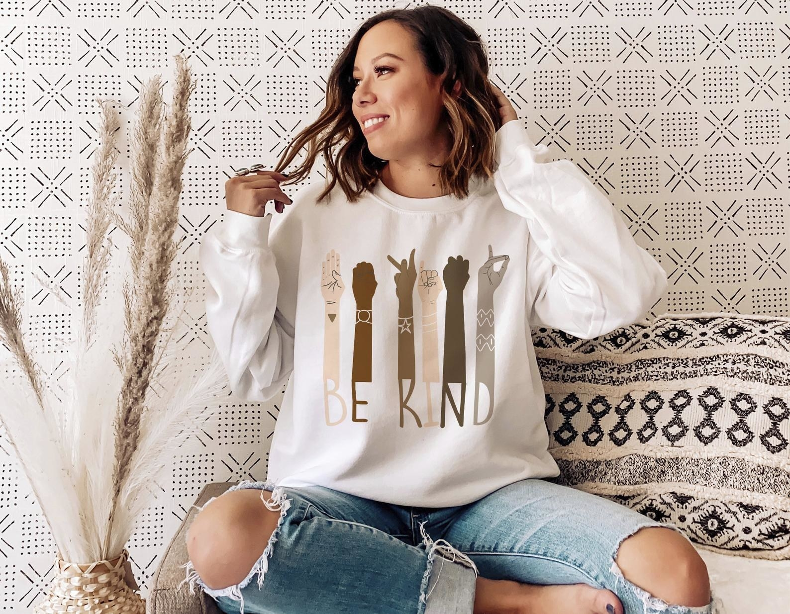 a model wearing the graphic crewneck sweatshirt in white that reads be kind and has different color arms signing each letter
