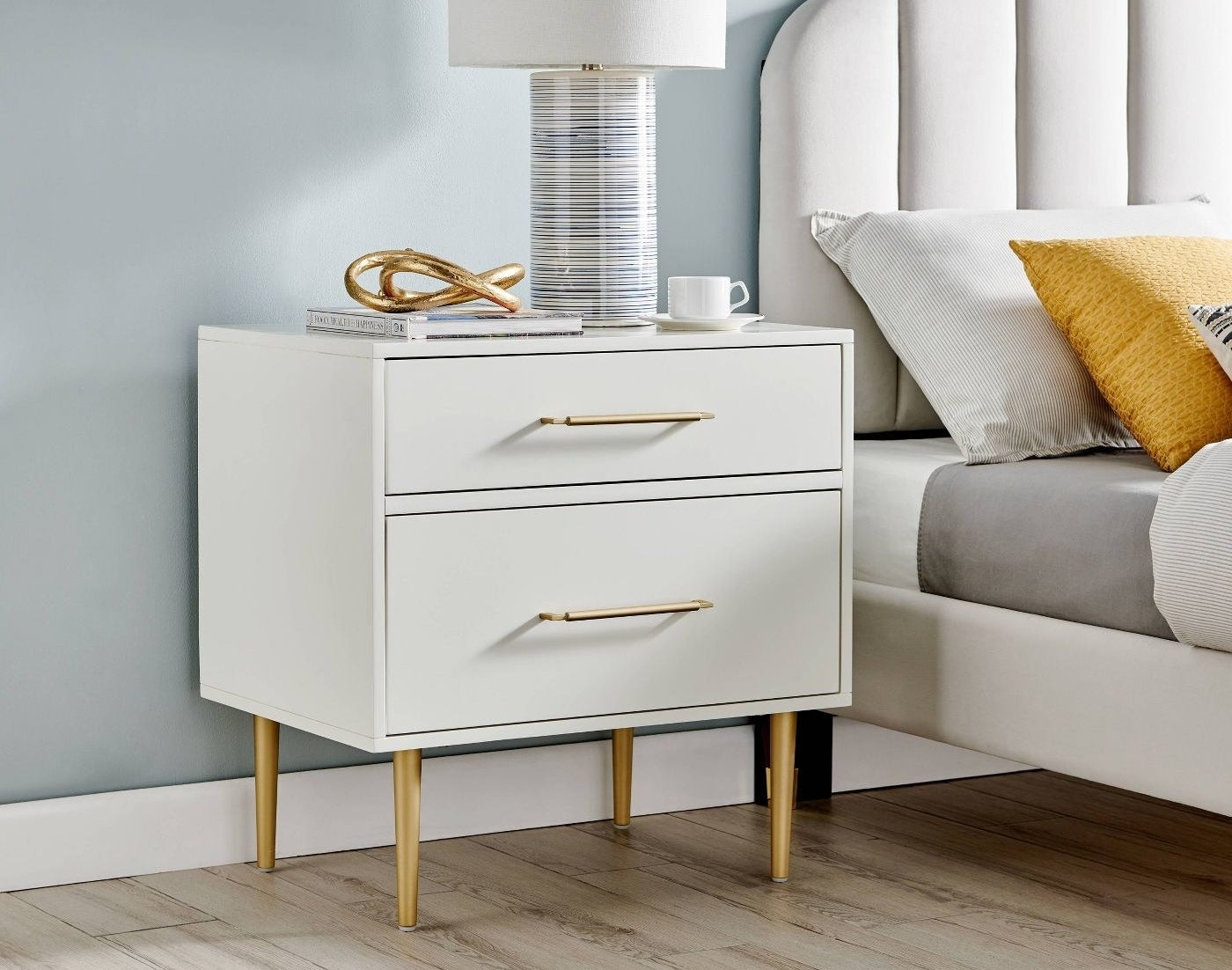 A white two drawer nightstand with brass handles and legs