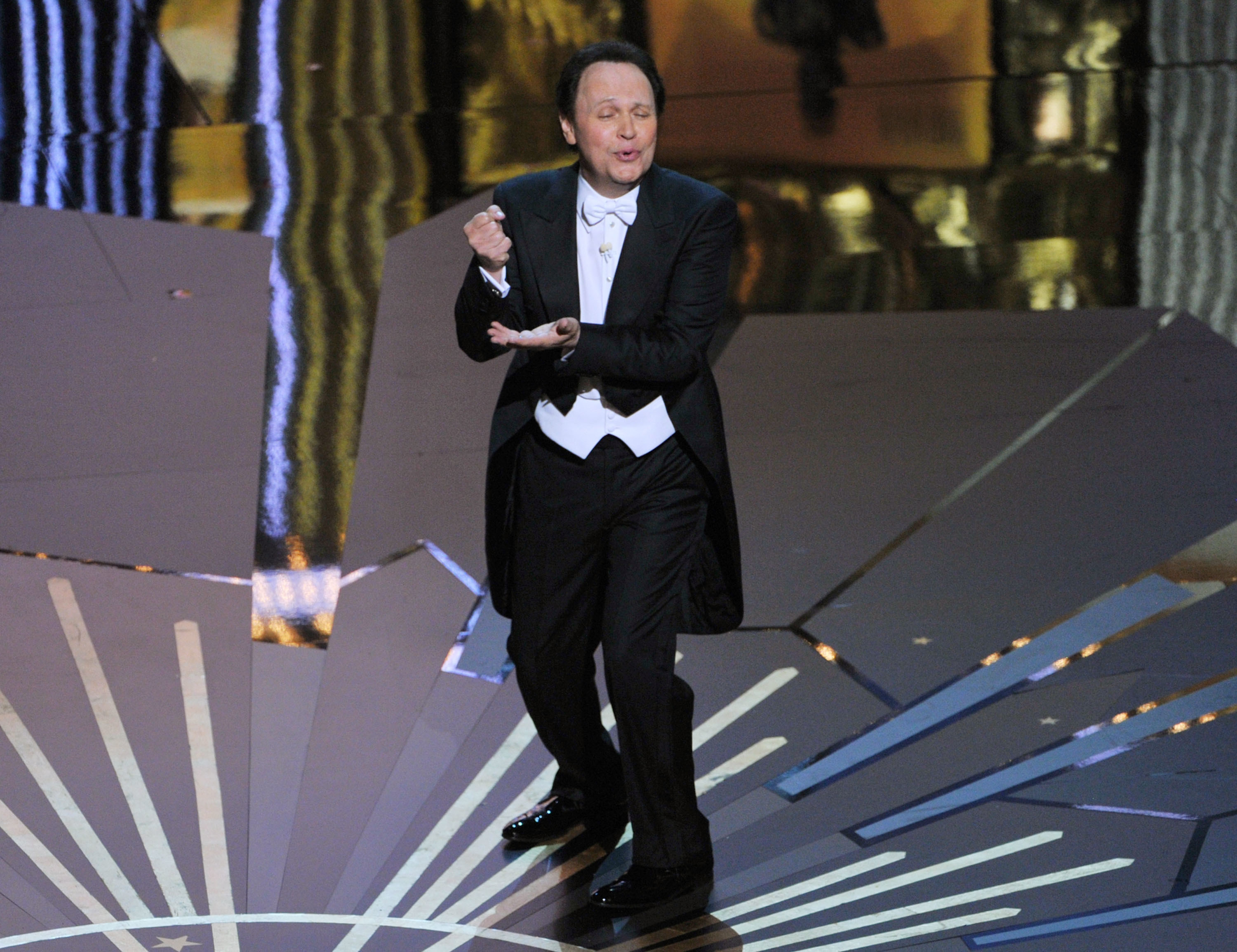 Billy Crystal performing onstage at the Oscars