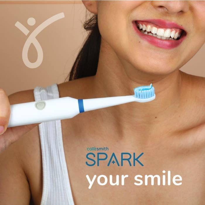 A woman smiling with the toothbrush in her hand