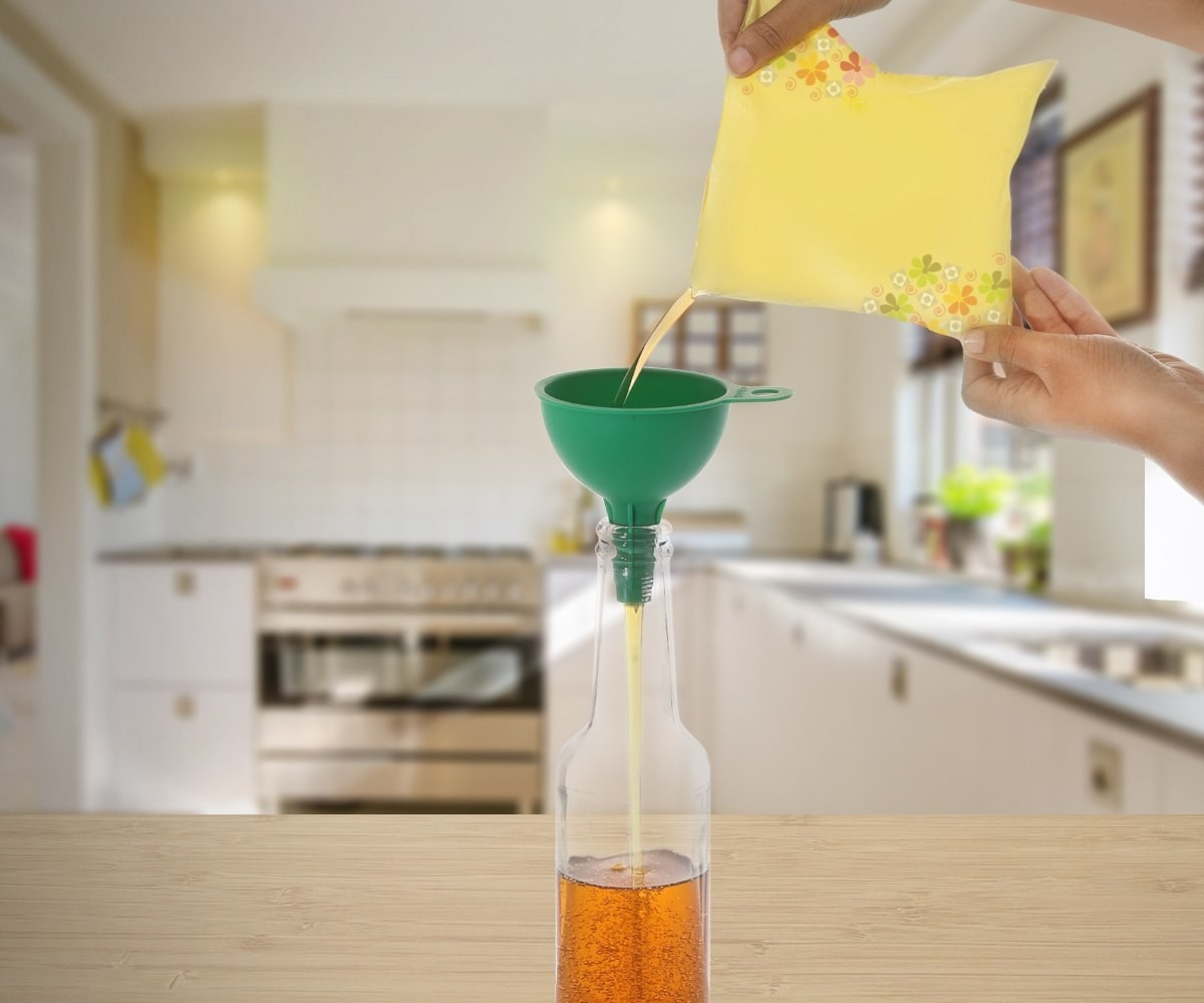 A person pouring a bag of oil in a bottle using the funnel