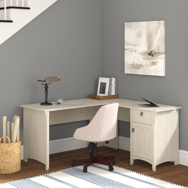 "The desk in white, with a full desk area on one side of the ""L"" shape, and a cabinet with small drawer at the end of the other side of the ""L"""