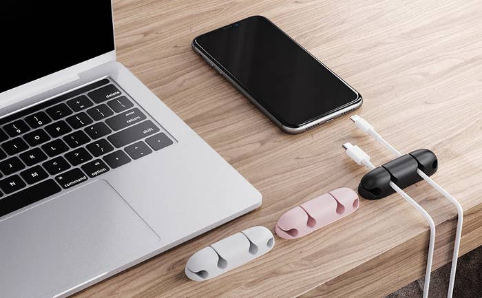 Three cable holders on a desk with wires running through one of them, next to a laptop and a phone