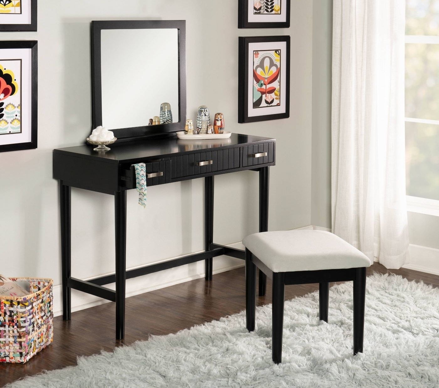 A black vanity with a square mirror and stool