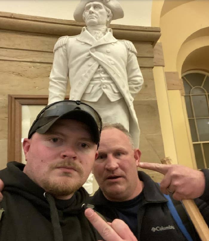 Two white men take a selfie in front of a statue, one flipping off the camera and the other pointing at him