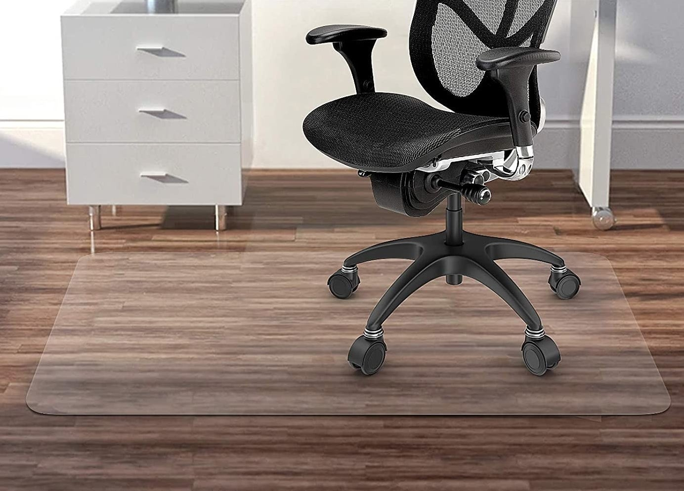 The clear mat in a home office with a rolling office chair on top