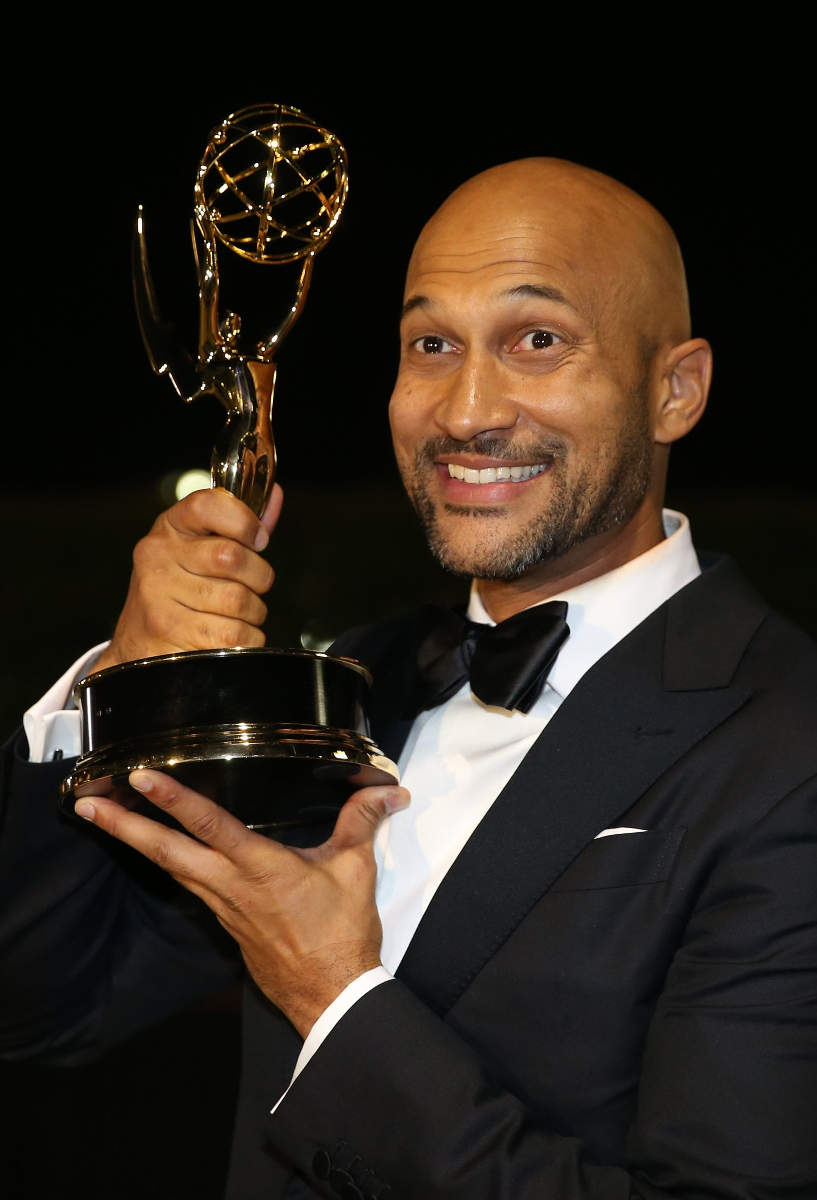 Keegan-Michael Key in a suit, smiling and holding his Emmy Award