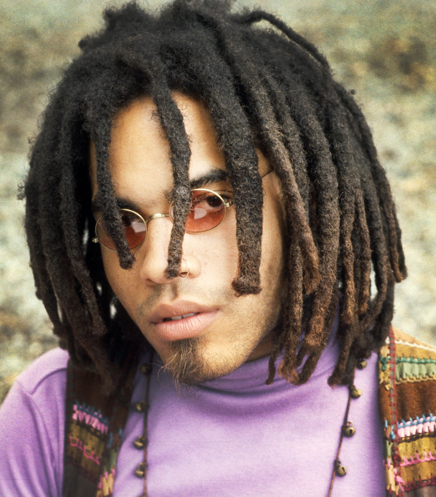 Lenny Kravitz with shorter dreads and sunglasses, wearing a purple turtleneck and striped vest
