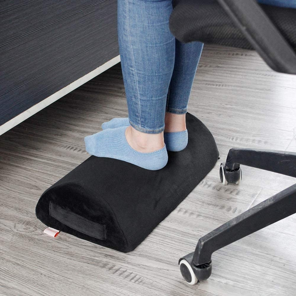 A person sitting at an office chair with their feet rested on the cushion
