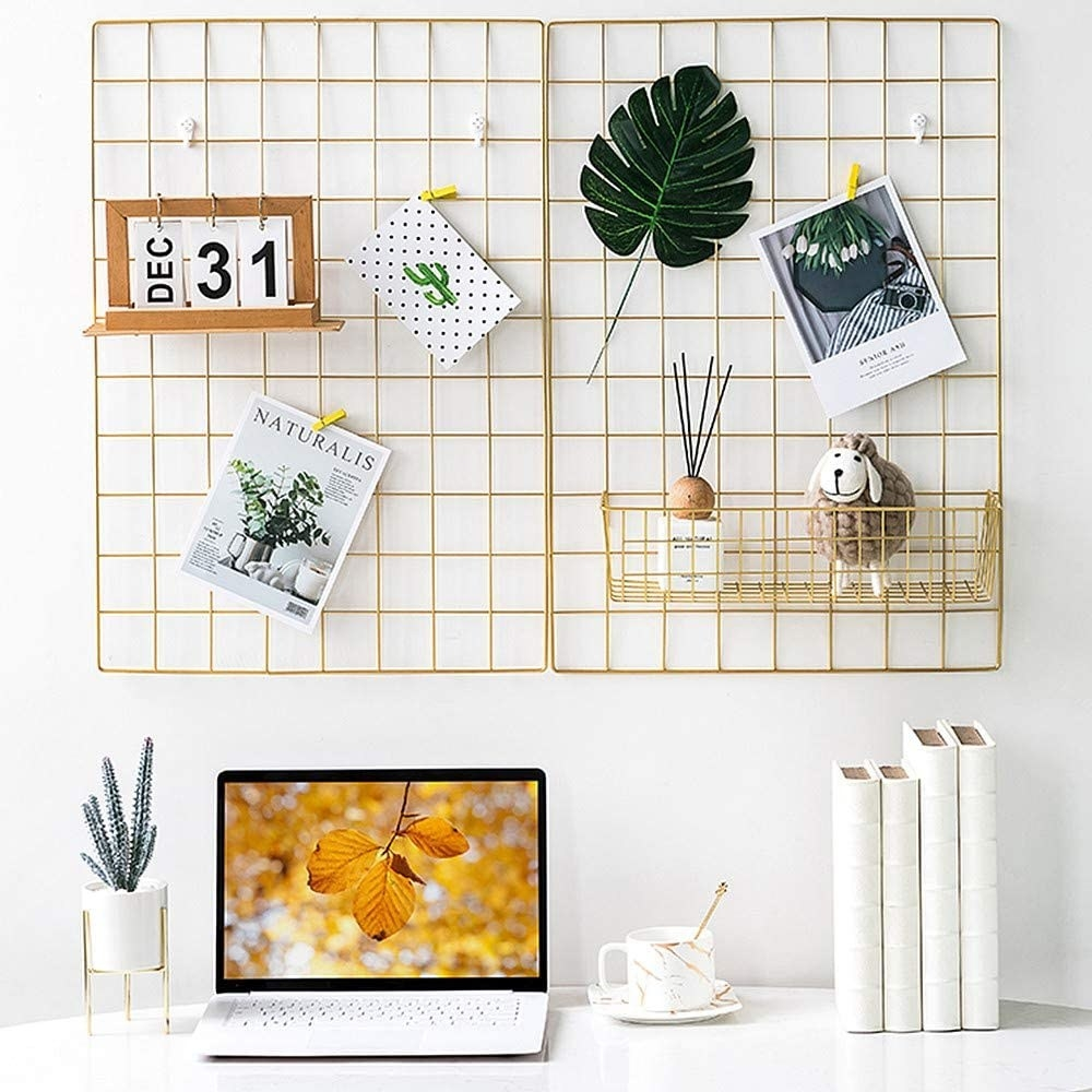 The grid wire panel on a wall with memos and decoration hanging off of it above a desk with a laptop on it