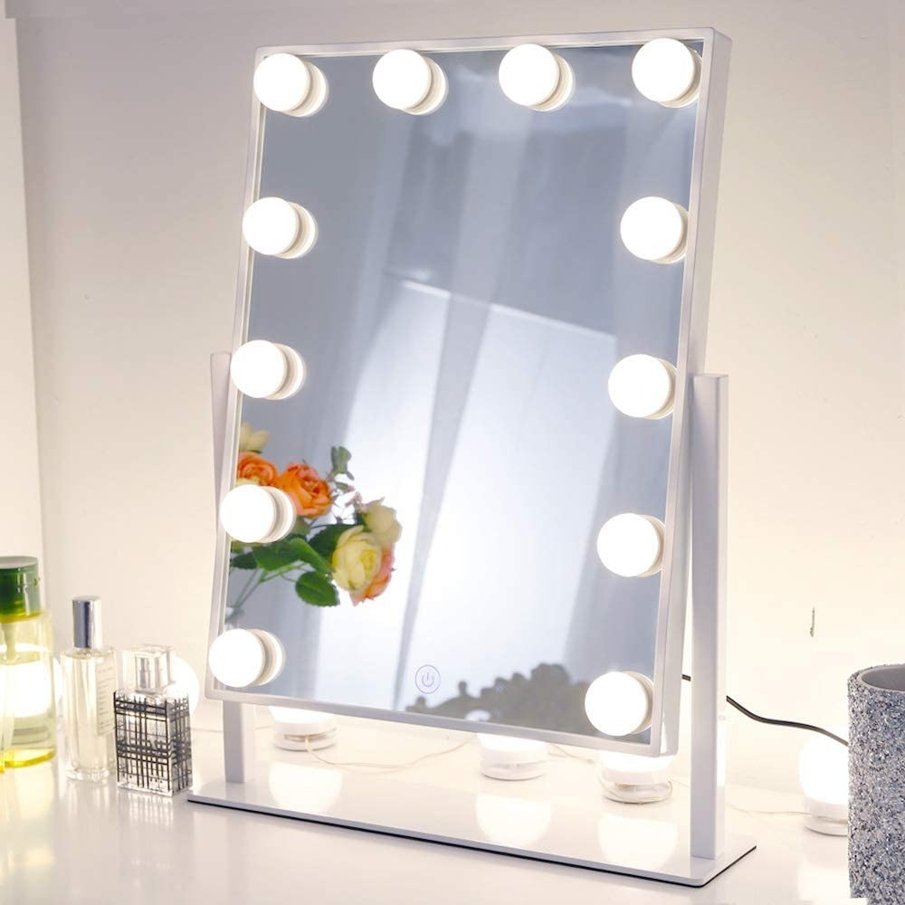 the mirror on a desk next to some perfume bottles
