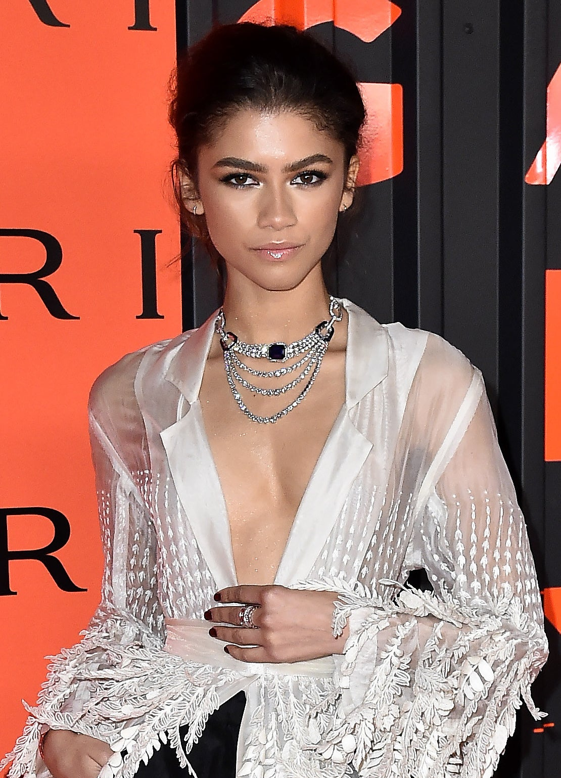 Zendaya at a BLVGRI event, wearing a V-neck blouse and her hair up