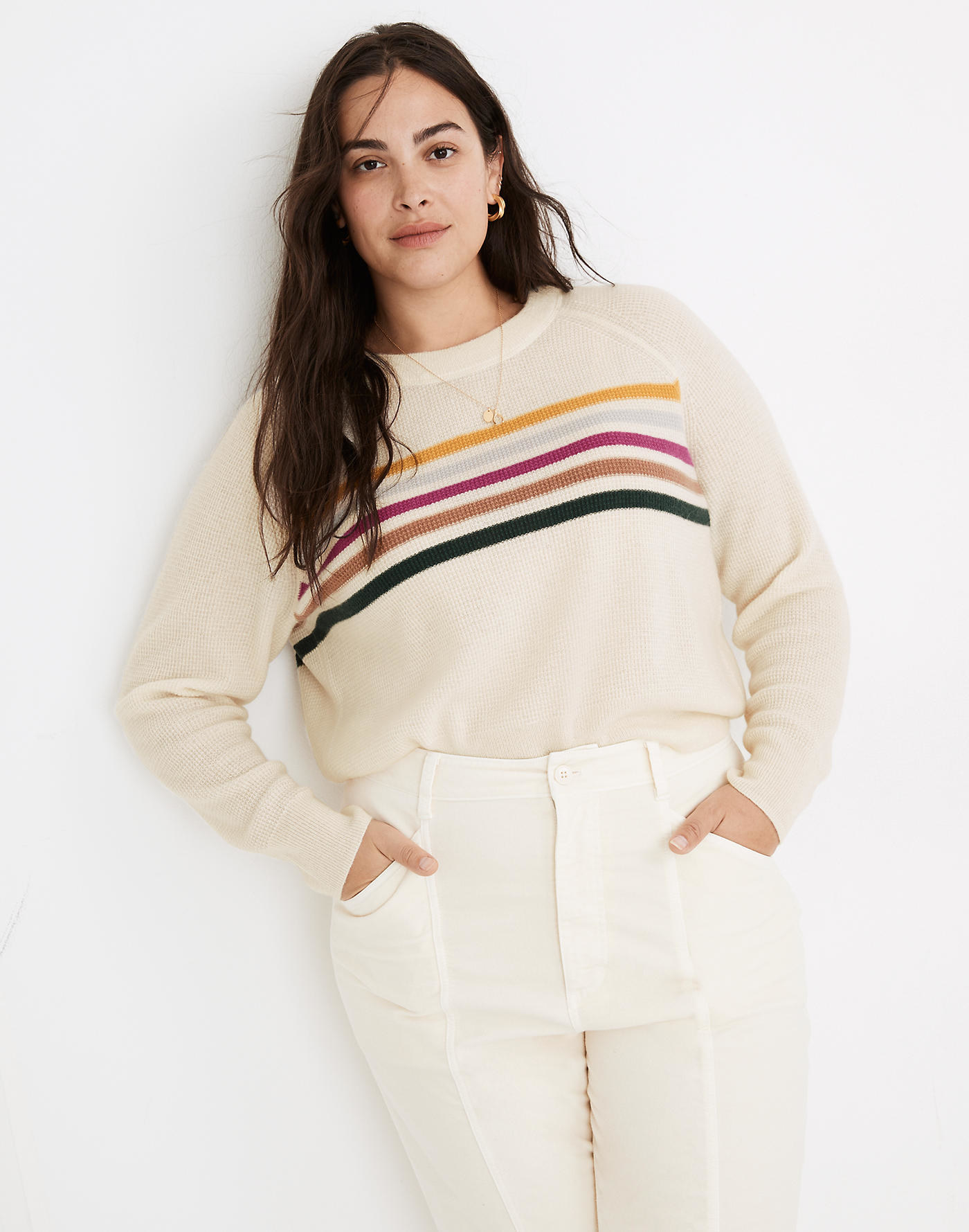 Model wearing a cream sweater with stripes