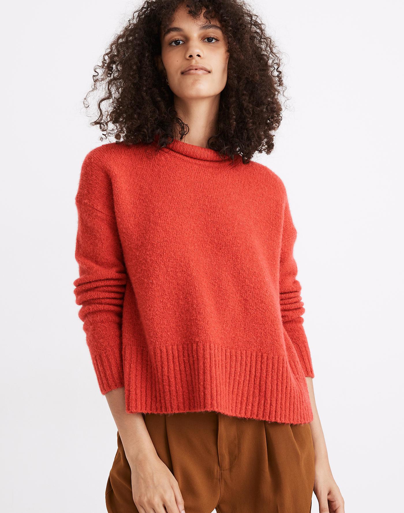 Model wearing red-orange pullover