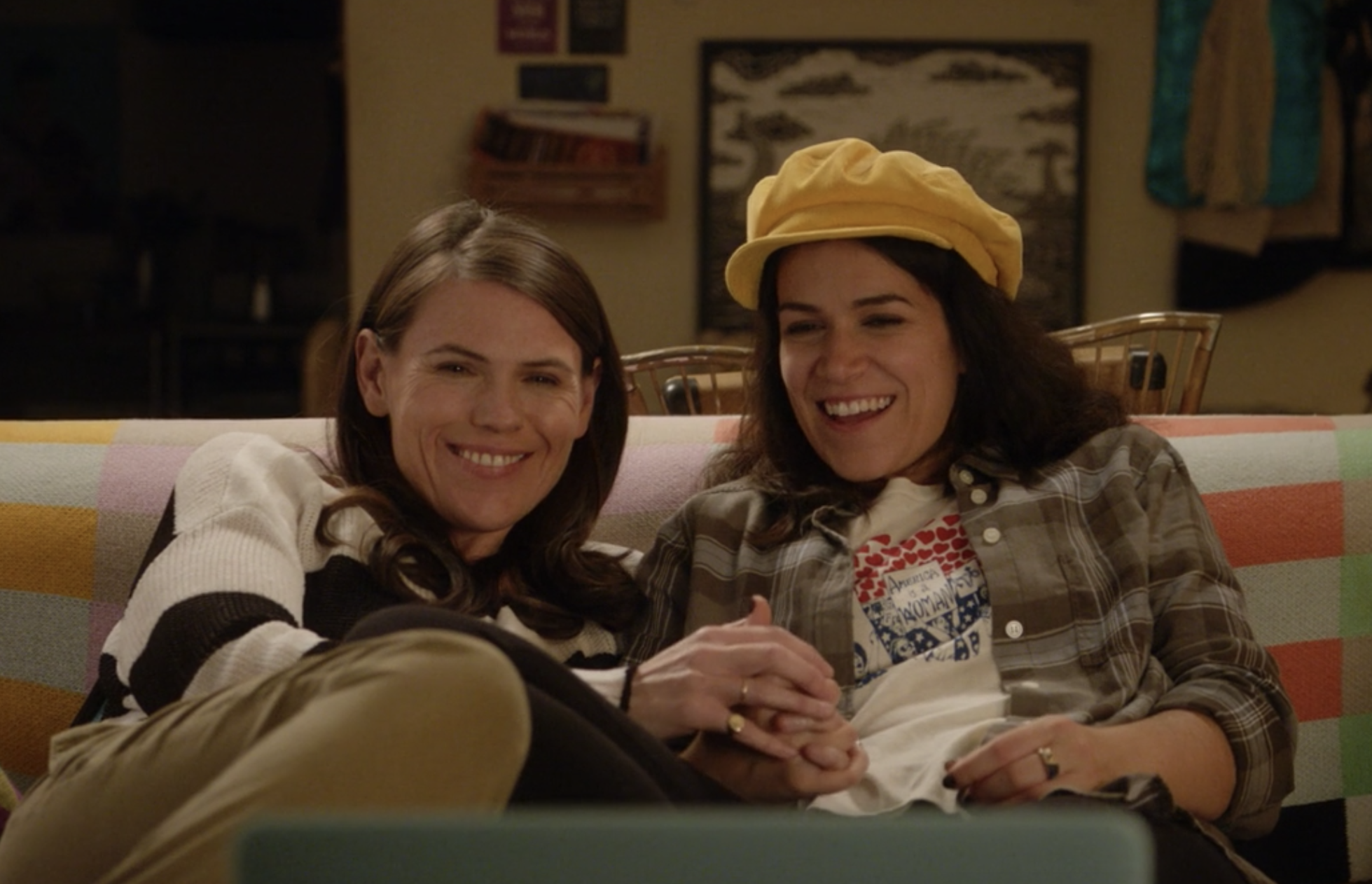 Abbi and Leslie watching TV while holding hands