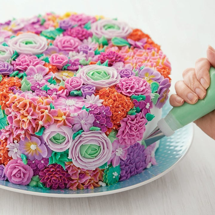 Person decorating cake with multicolored frosting flowers
