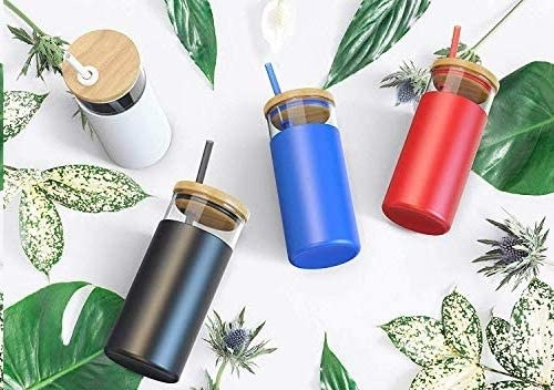 Four tumblers of various colours on a leafy backdrop