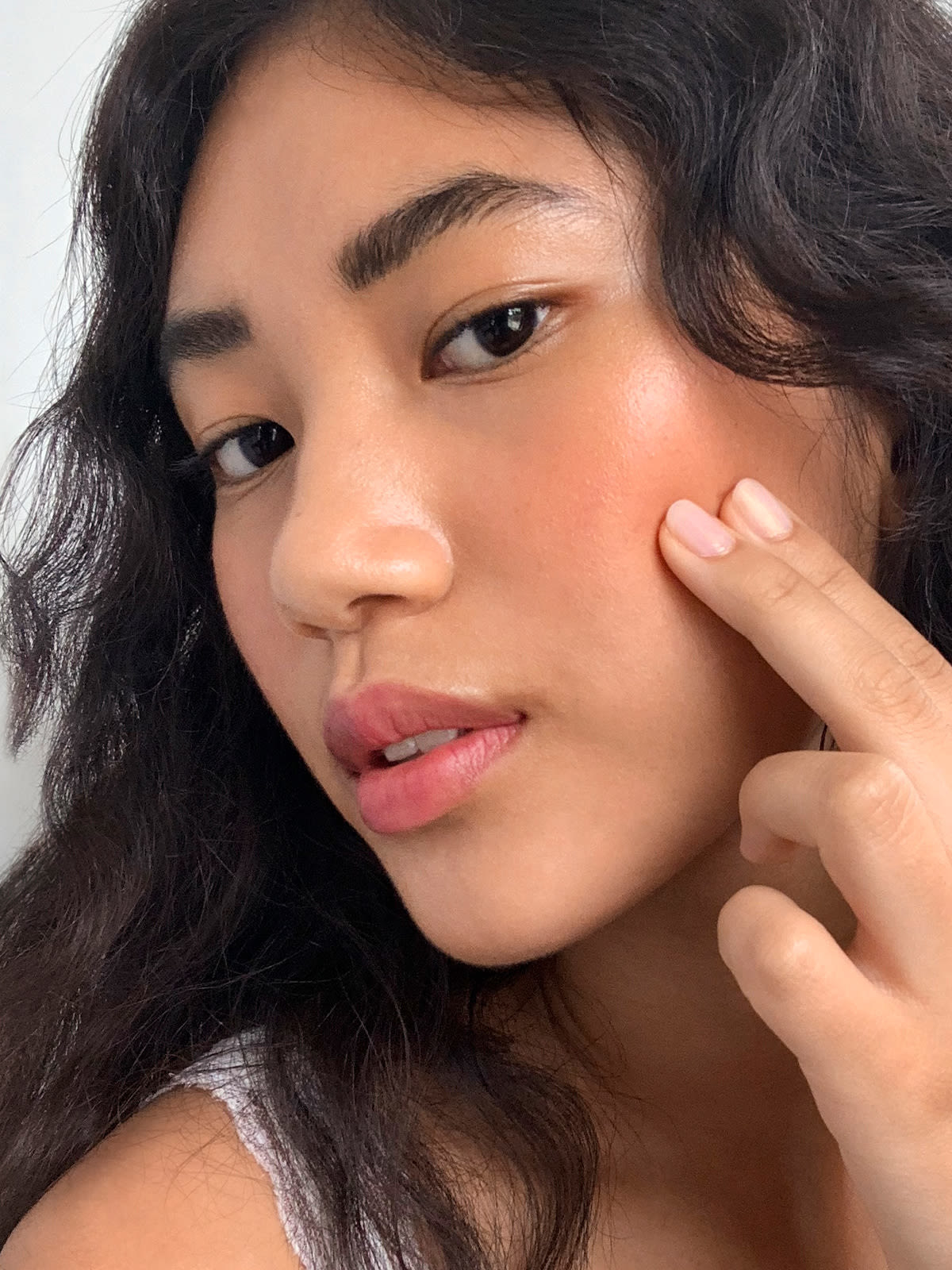 Model applying the blush with two fingers