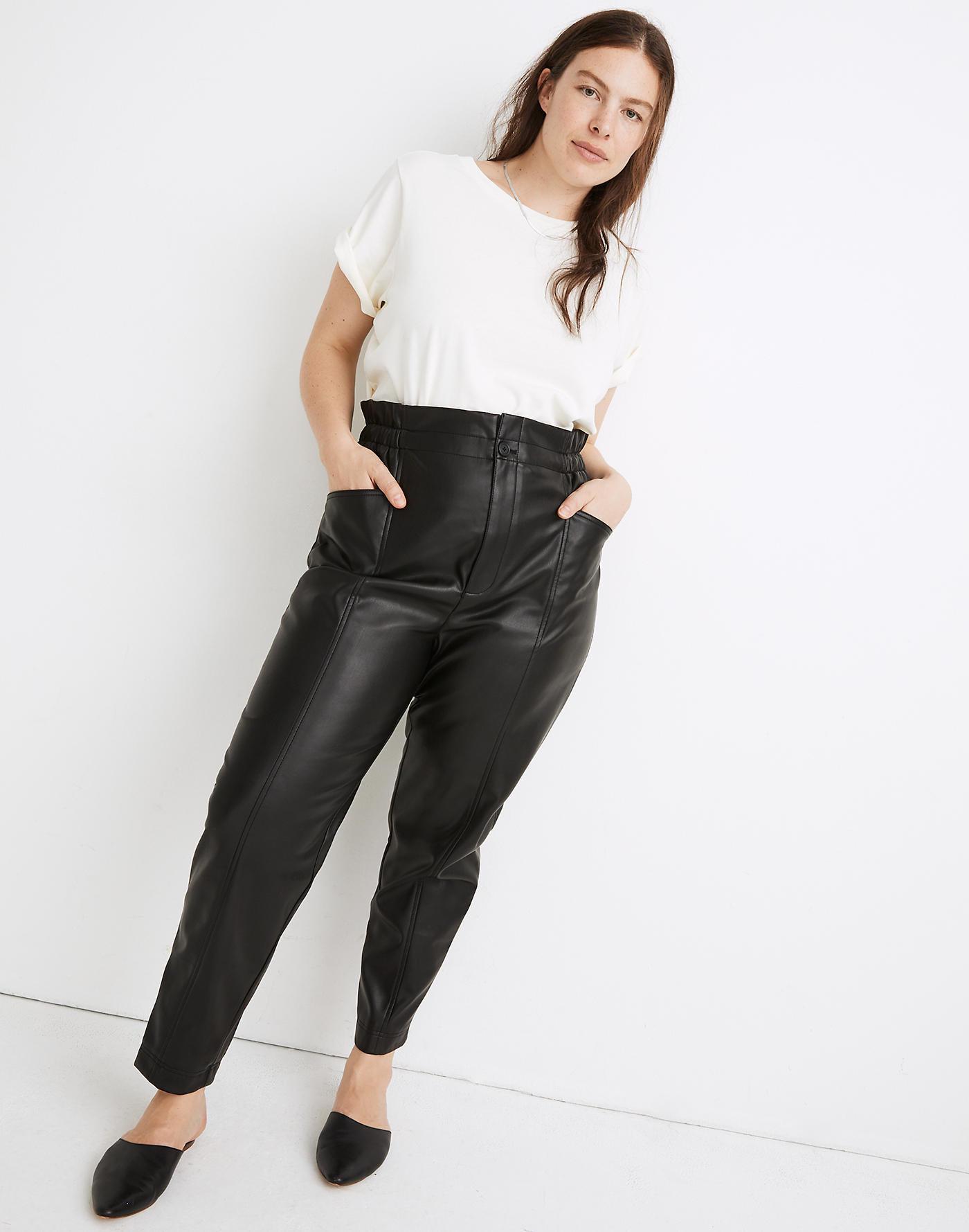Model wearing black faux leather pants