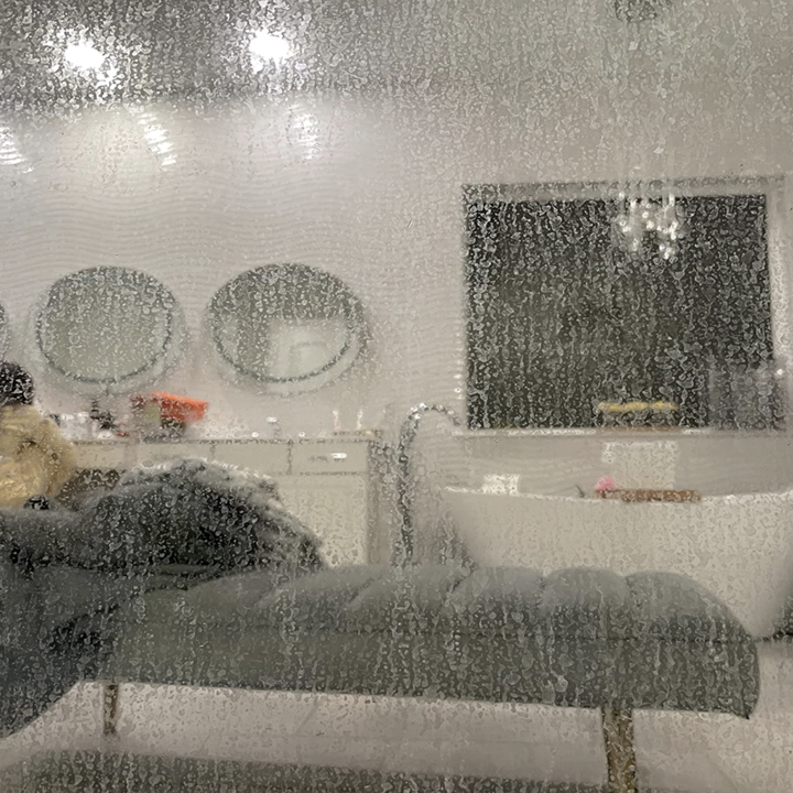 a reviewer's glass shower door looking fogged up from hard water stains