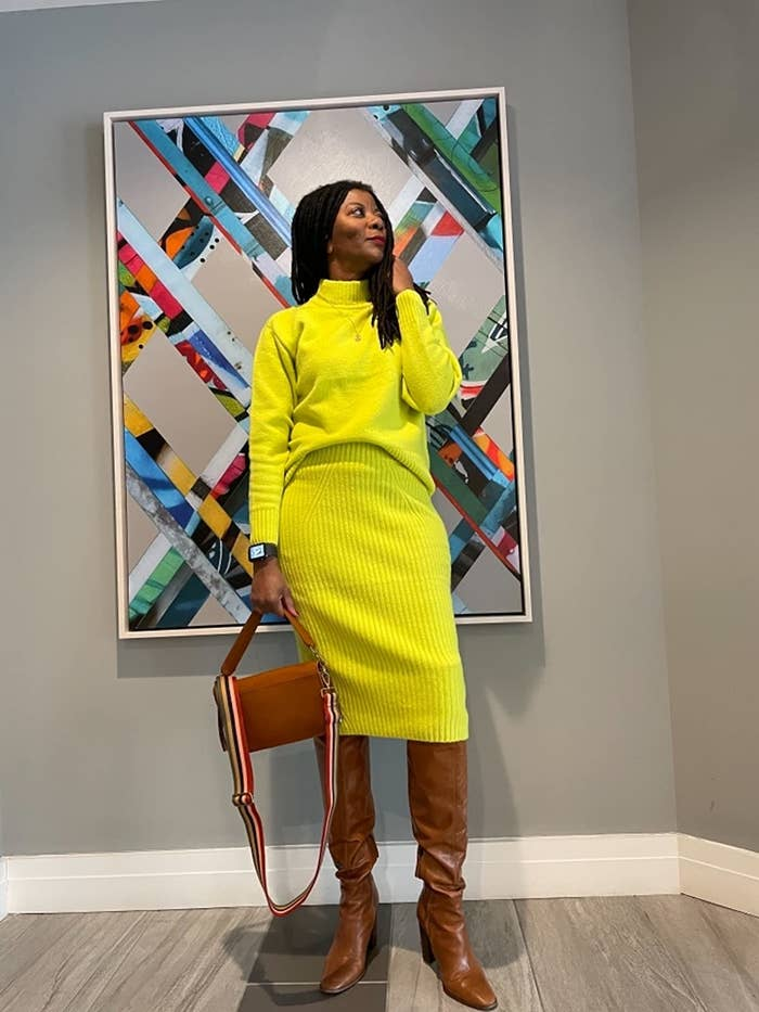reviewer wearing the ribbed pencil skirt and crewneck sweater in bright yellow