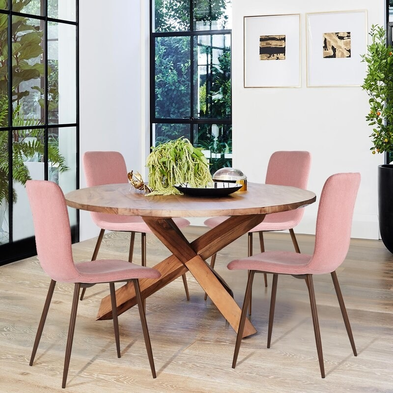 A set of four chairs in pink, with splayed legs in walnut