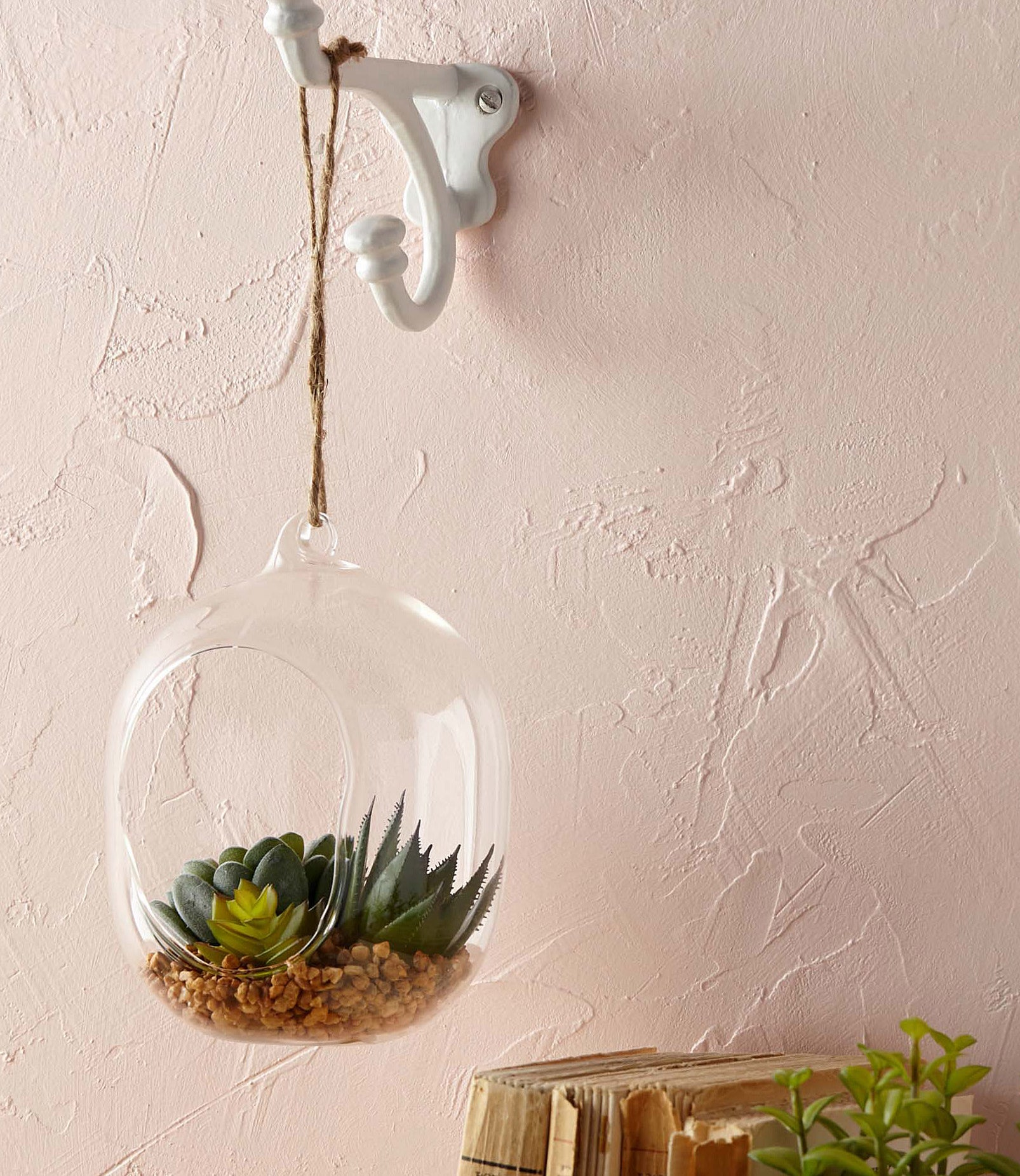 A glass terrarium hanging in front of a textured wall
