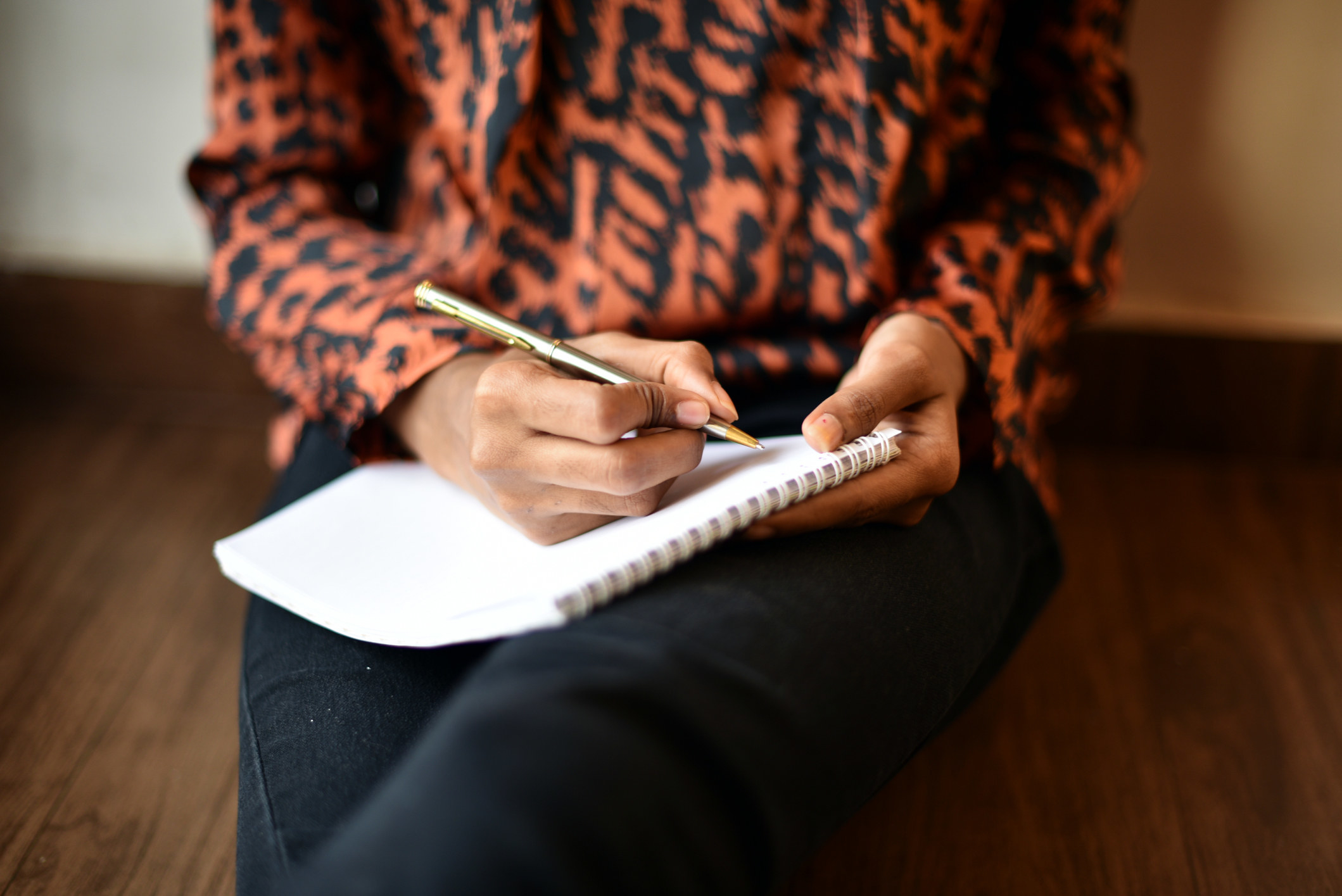 A woman sitting on the floor journaling.