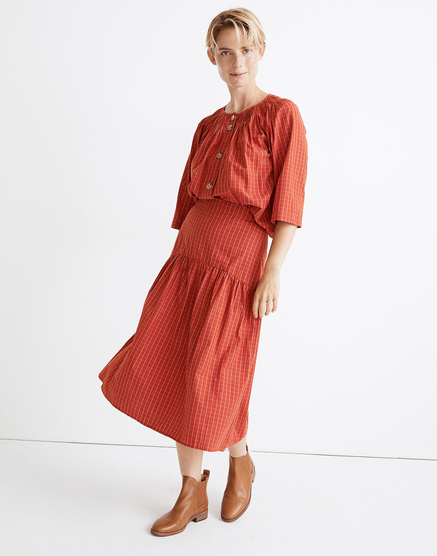 Model wearing red plaid skirt