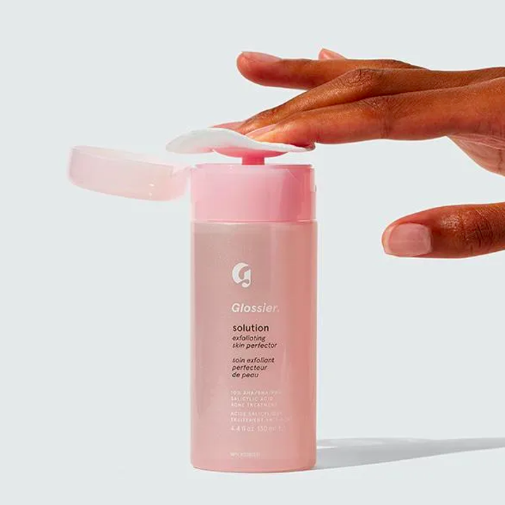 A person pressing a cotton pad into the bottle of Glossier Solution