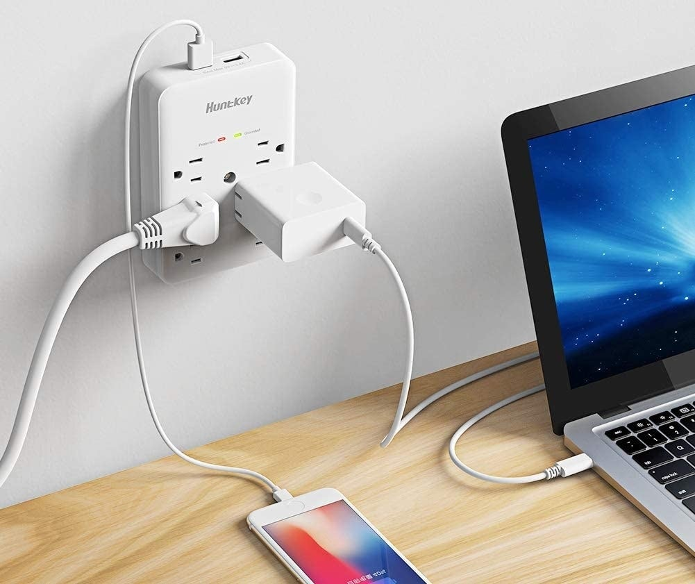The charging port on a wall above a desk, charging multiple devices simultaneously
