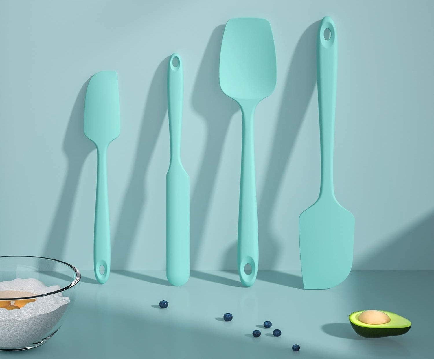 A set of four silicone spatulas leaning against a kitchen wall