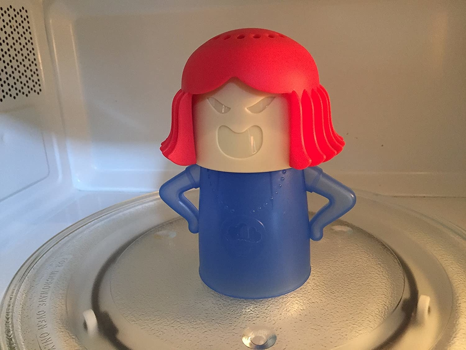 A tiny silicone steamer in the shape of a person with perforated holes on the top of their head sitting in a microwave