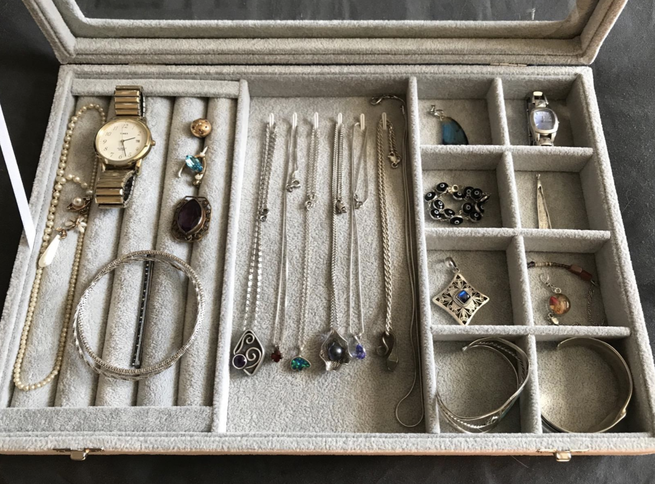 reviewer image of jewelry organizer holding a variety of jewelry types
