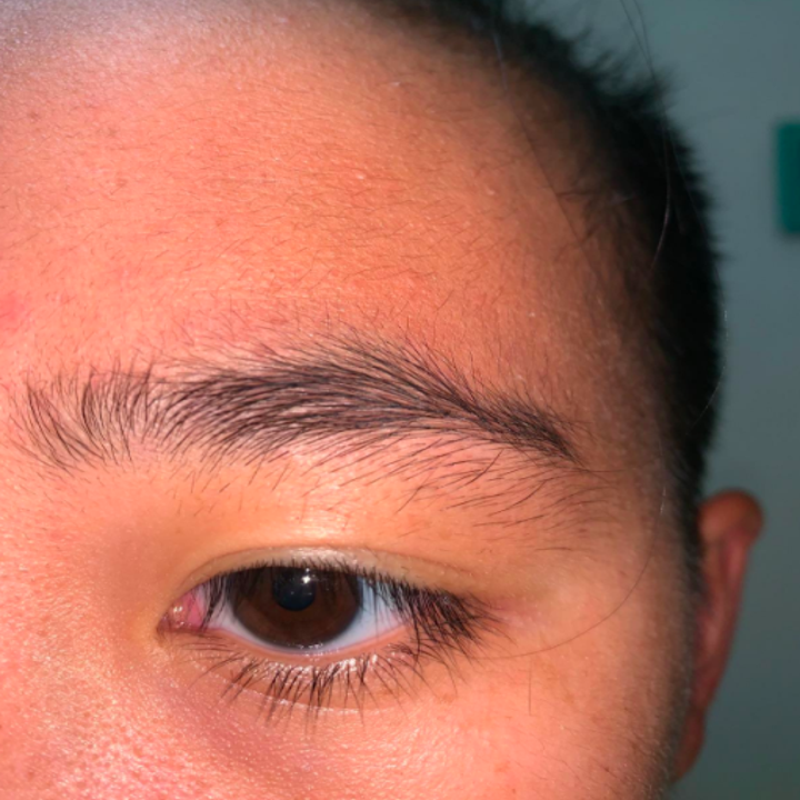 A reviewer showing the hair growing underneath their eyebrow before using the razor