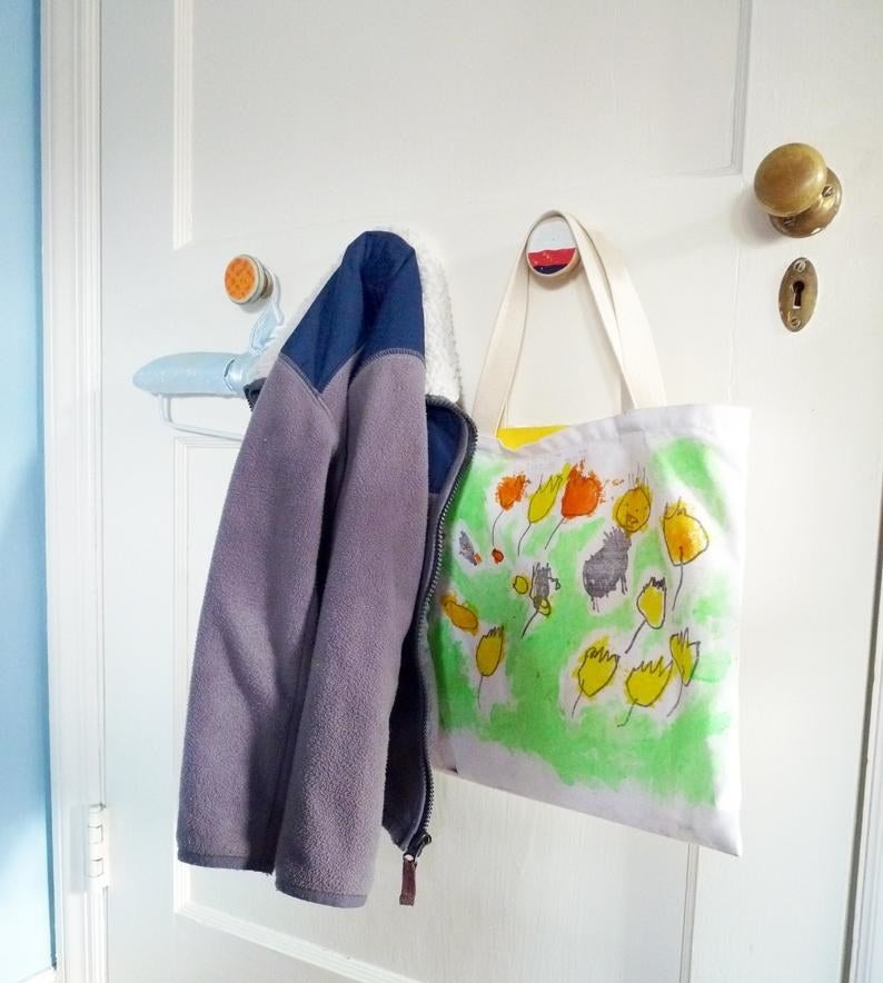 Colorful circle-shaped recycled hooks holding up a zip-up fleece and shopping bag