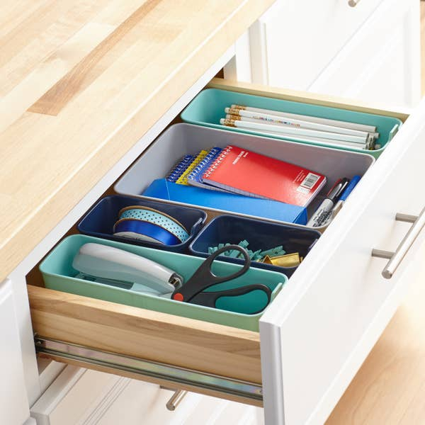 Multi-colored drawer organizers holding various office supplies inside a drawer
