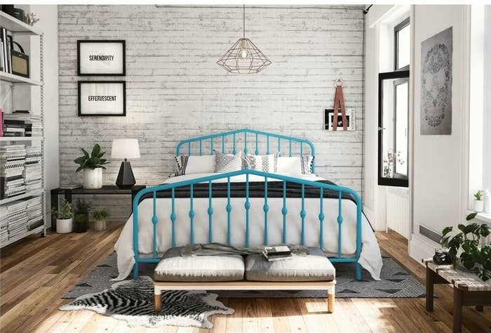 The bed frame in blue, with spindles on the headboard and footboard