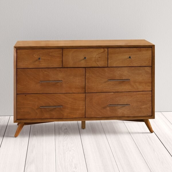 The dresser, which is rectangular, with two rows of two drawers, and three smaller drawers along the top of the dresser