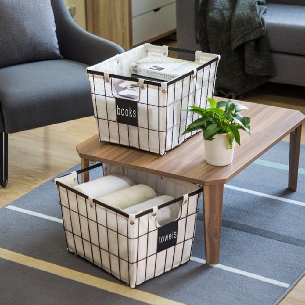 a lined, wire basket holding books sitting on a coffee table and another wire basket holding towels on the floor