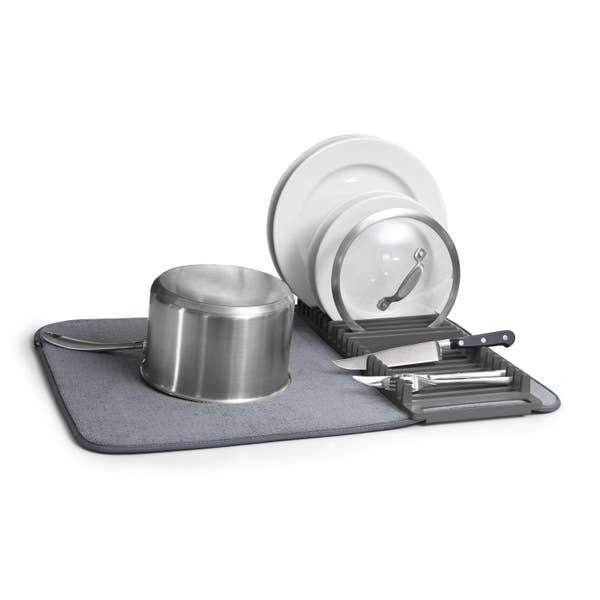 grey dish drying rack with pot, plates, and utensils on top