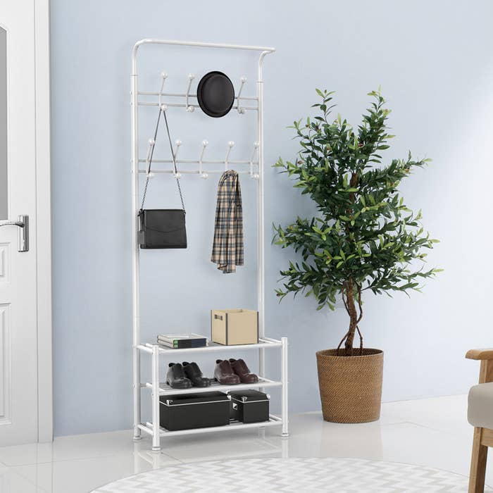 white hall tree with accessories and coat hanging on the racks and shoes and boxes on the shelves below