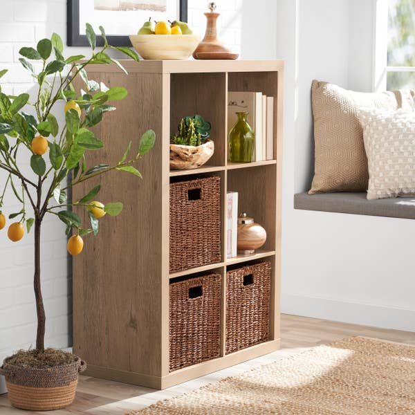 natural wood colored organizer with books and storage bins inside