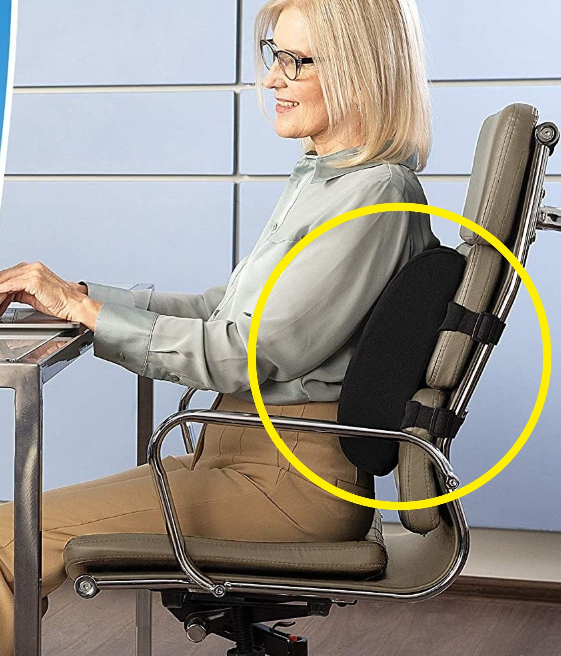 Someone sitting in an office chair leaning against the supportive back cushion