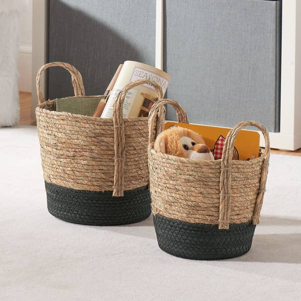 two different sized natural and black colored baskets with handles and items inside