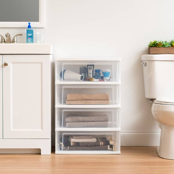 plastic four-drawer storage chest with towels and bath products inside, sitting in a bathroom