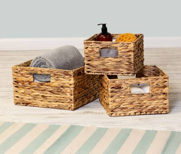 Three woven baskets with miscellaneous bath products inside