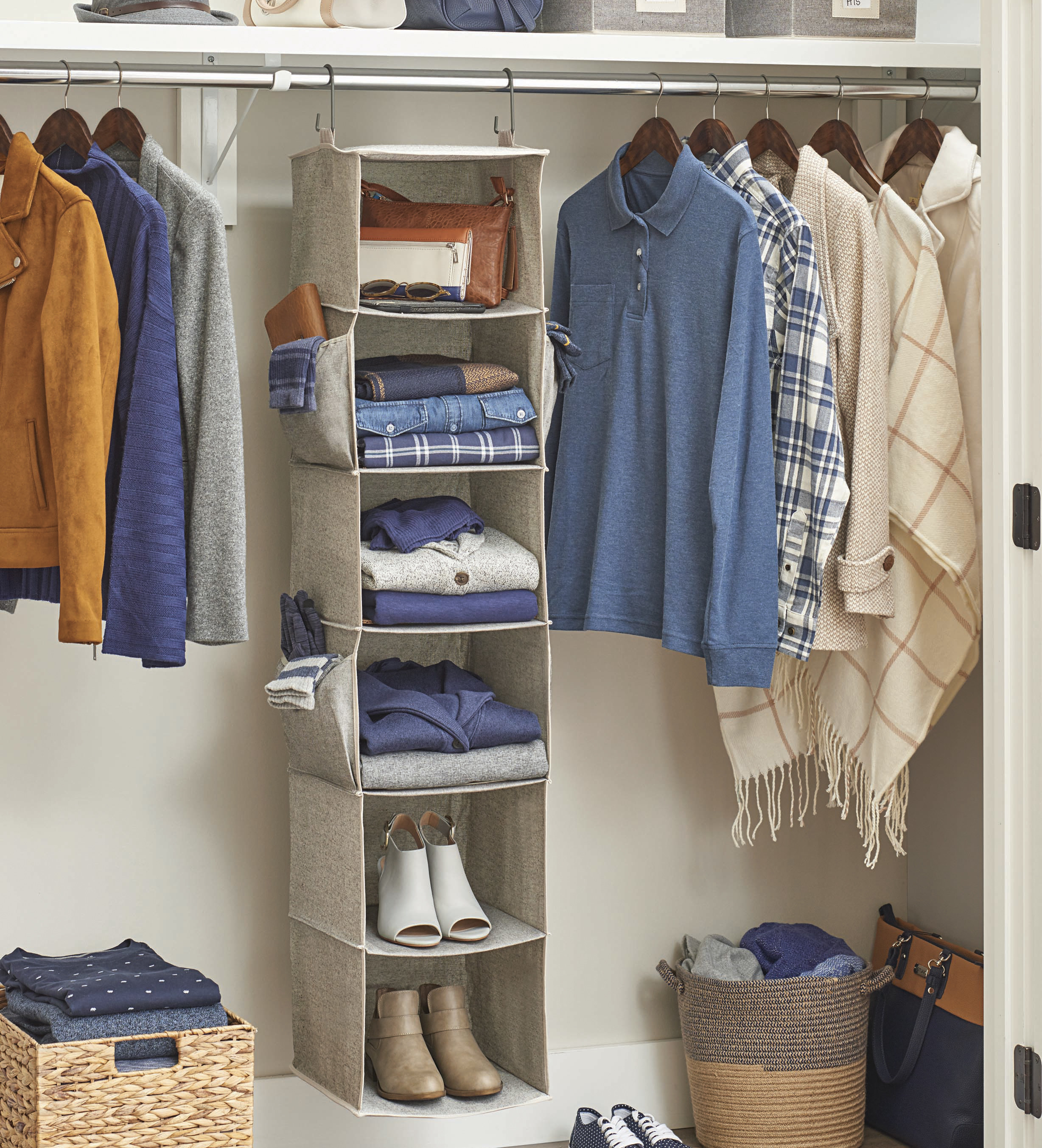 Hanging closet organizer inside a closet with accessories, clothes, and shoes on the shelves