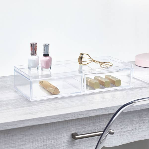 clear two drawer organizer with nail polish and eyelash curler on top and lipsticks inside the drawers